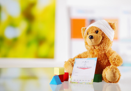 Ill Teddy Bear with Bandage Sitting on a Glossy Table with Medical Report Card and Colored Shape Blocks