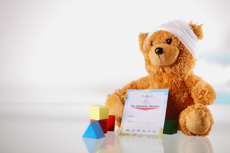 stuffed animals: Close up Bandaged Teddy Bear Toy, Medical Report Card and Colored Shape Blocks on a Glossy Table with White Background. Stock Photo