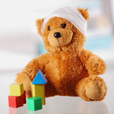 pediatrist: Close up Classic Brown Teddy Bear with Bandage on the Head Sitting on the Table with Assorted Block Shapes. Stock Photo