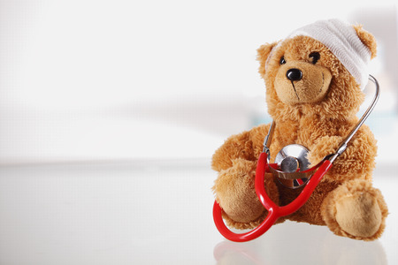 Close up Bandaged Teddy Bear on the Table Top with Stethoscope Device on White Background, Emphasizing Copy Space on the Left Side.