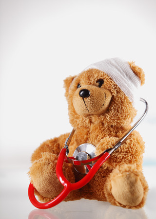 sick teddy bear: Conceptual Sick Brown Teddy Bear with Bandage on the Head and Checking Himself with Stethoscope Device. Isolated on White Background.