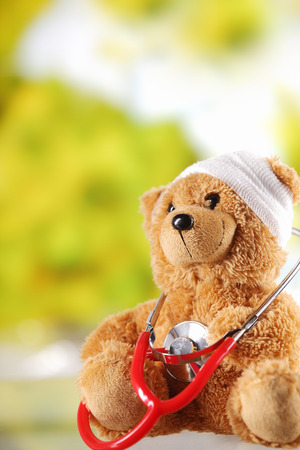 sick teddy bear: Conceptual Sick Brown Plush Teddy Bear Toy with Stethoscope Device Around the Neck