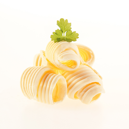 Rolled coils of fresh creamy butter garnished with parsley for a gourmet food presentation isolated on white