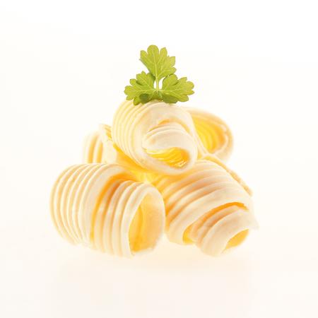 Warmgewalste coils van verse romige boter gegarneerd met peterselie voor een gastronomische presentatie op wit wordt geïsoleerd