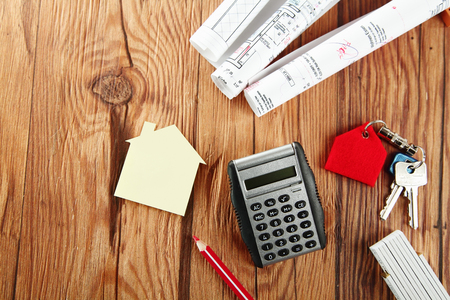 Conceptual Calculator Device on Top of Wooden Table with Paper Model House, Keys, Rolled Building Plan and a Pencil on Top of a Wooden Table. photo