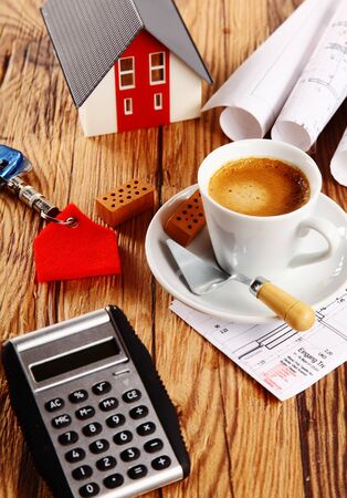 bickie: Close up Espresso, Mini House and Calculator Device on Wooden Table with Small Wooden Bricks, Key Holder and Trowel Tool for Realty Concept.