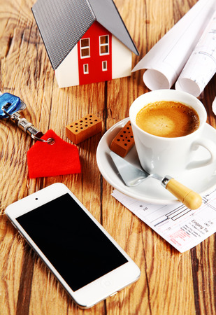 bickie: Close up Brown Coffee, Mini House, Rolled Sketch and Mobile Phone on Wooden Table with Small Wooden Bricks, Key Holder and Trowel Tool for Real Property Concept.