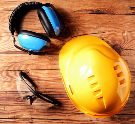 high visibility: Close up Safety Helmet, Goggles and Ear Defenders for Engineers on Top of Brown Wooden Table