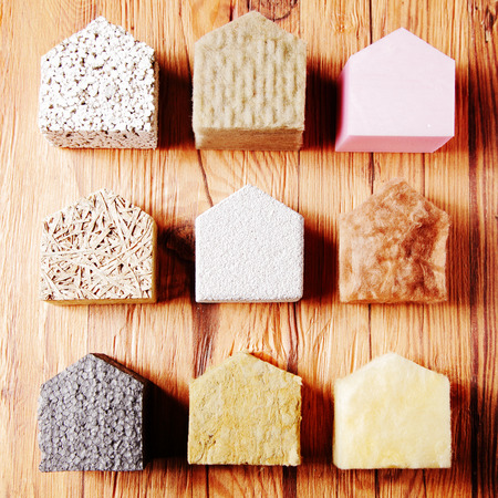 insulant: Close up Aligned Small Model Houses with Various insulation on Top of the Wooden Table