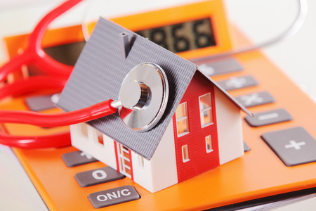Close up Miniature Model Home with Stethoscope Device on Top of a Calculator on White Table.