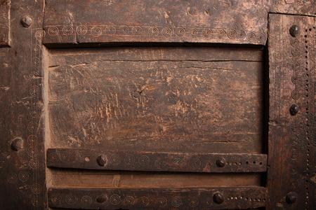 古い傷のひびの入った着用木製パネル十字棒とテクスチャ、アフリカの手工芸品のスタッド、フルフレームをテクスチャの詳細を閉じる
