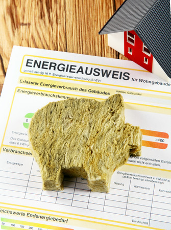 rockwool: Energy saving concept with a piggy cut out of rockwool insulation lying on a household energy efficiency report conceptual of saving costs through insulation