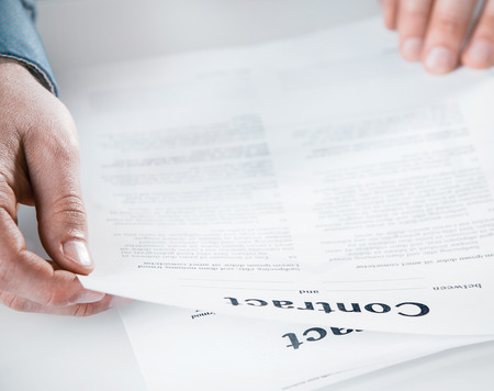 fine print: Businessman reading through a legal contract at the office before signing to close the agreement, close up view of his hands and the document Stock Photo
