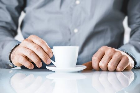 addictive drinking: Businessman enjoying a coffee break sitting at his desk drinking a cup of hot beverage, close up conceptual image of his hands