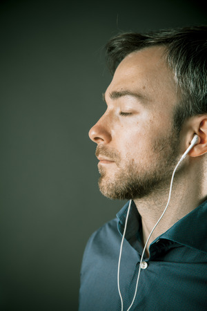 contentment: Blissful young man listening to music on a set of ear plugs standing with his eyes closed in contentment, close up profile view on grey Stock Photo