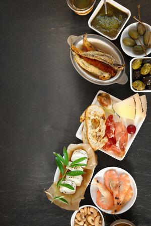 jamon y queso: Aperitivos gourmet surtidos visto desde arriba con gambas, sardinas, jamón de Parma, aceitunas, nueces de anacardo, el queso de leche de cabra en platos individuales con copyspace a la izquierda