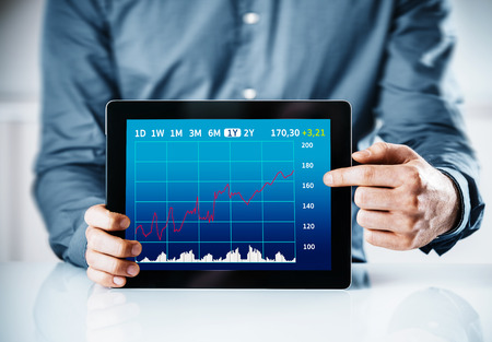 Man pointing to a business graph on a tablet displaying a monthly time line and statistics or projections in an analysis or presentation concept photo