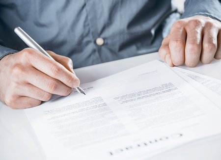 legal document: Businessman signing a legal document with text with a silver fountain pen, close up of his hands as he sits at a desk Stock Photo