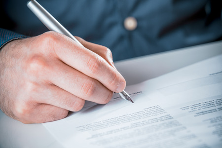 Close up of the hand of a man signing a business contract or document with printed text using a fountain pen photo