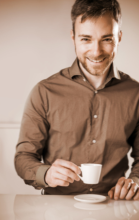 shirtsleeves: Faded effect image of a smiling happy bearded young man in a brown shirt enjoying a cup of coffee sitting at a table looking at the camera with a beaming grin