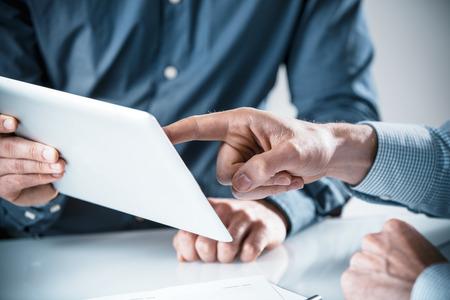 reuniones empresariales: Dos hombres de negocios que tienen una discusi�n sobre la informaci�n muestran en un equipo Tablet PC, cierre para arriba de las manos apuntando a la pantalla en un concepto de trabajo en equipo