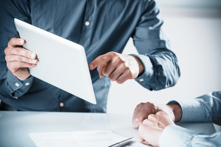 Two businessmen in a meeting discussing a projet on a tablet computer pointing to the screen, close up of their hands Stock Photo