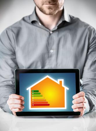 eficiencia energetica: Tabla de eficiencia energética aparece en un equipo Tablet PC rating el consumo y la eficiencia de la energía y el poder en una vivienda privada en poder de un hombre