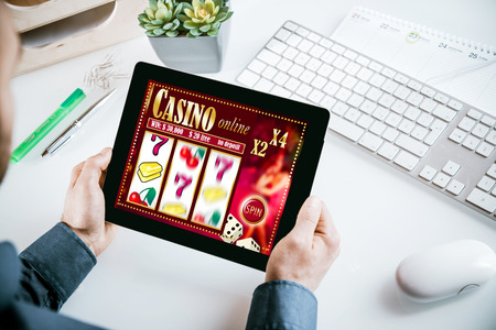 Online casino gambling interface on a tablet showing lucky numbers 777 out of sequence held by a businessman in his office in a gambling addiction concept