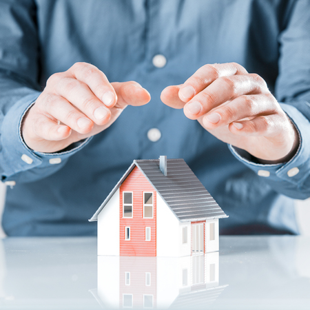 investment protection: Man protecting his house with cupped hands conceptual of insurance, risk, security, investment, protection and ownership Stock Photo