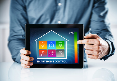 Man pointing to an online interface for a smart house with a control panel with icons for lighting, temperature, security, wireless, power and an eco energy chart Фото со стока