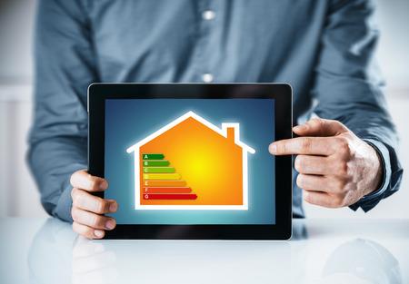 energy saving: Hombre que señala a una eficiencia energética tabla de clasificación en línea para una casa muestra en la pantalla de un ordenador tableta, cierre para arriba de las manos