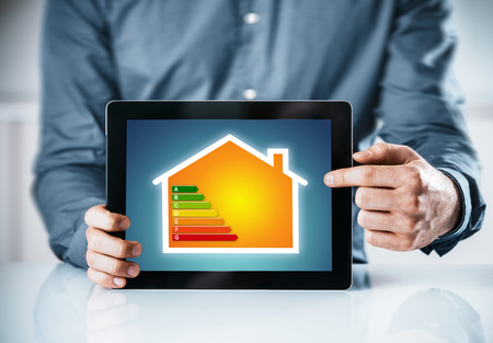 Man pointing to an online energy efficiency rating chart for a house displayed on the screen of a tablet computer, close up of his hands Stockfoto