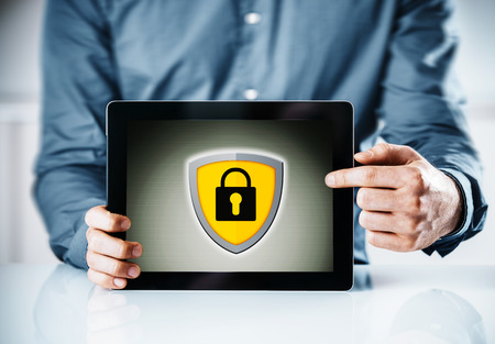 displaying: Online security concept with a man holding a tablet computer pointing to the screen displaying a yellow shield and padlock icon