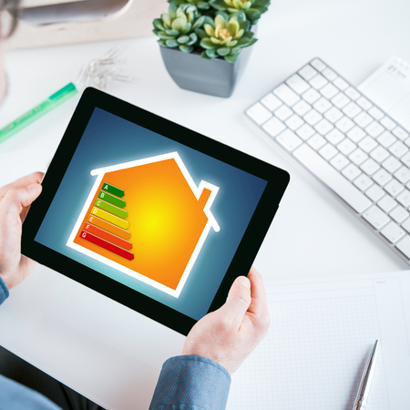 Smart home online energy efficiency rating chart displayed on the screen of a tablet held in the hands of a businessman sitting at his desk in the office