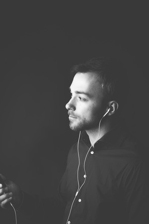 listening device: Man listening to music on an MP3 player standing holding the device in his hand listening to the tunes over earplugs, greyscale image with copyspace