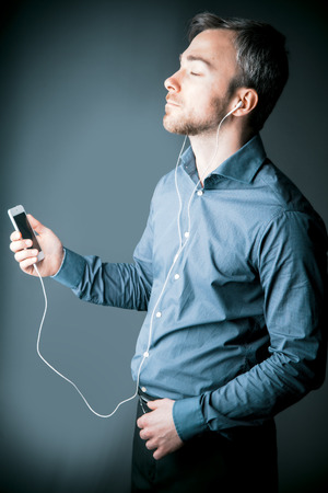 Young man absorbed in his music holding an MP3 storage device in his hands listening over ear plugs with his eyes closed in contentment