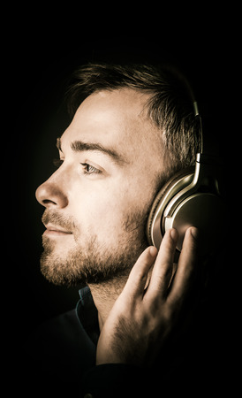musing: Attractive bearded young man musing as he listens to his music on stereo headphones looking off to the left in profile with a serene dreamy expression, close up of his face on a dark background Stock Photo