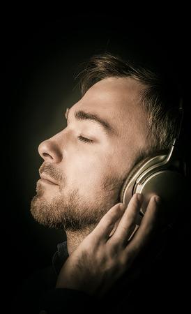 éxtasis: Joven atractivo contento de escuchar su música en los auriculares estéreo con los ojos cerrados en el placer, la vista lateral del primer de la cara sobre negro