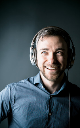 listening to music: Charismatic happy man enjoying his music laughing as he listens to the soundtracks on stereo headphones, head and shoulders portrait Stock Photo