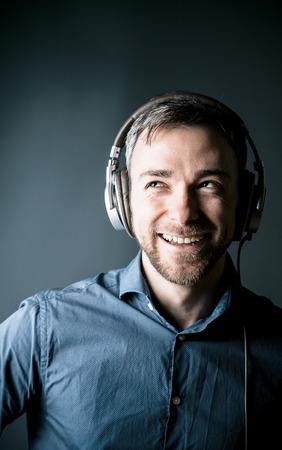 personas escuchando: Hombre feliz disfrutando de su m�sica Carism�tica riendo mientras escucha a las bandas sonoras de los auriculares est�reo, la cabeza y los hombros retrato Foto de archivo