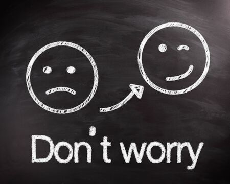 Two Smileys Drawing on Black Chalkboard for Dont Worry Concept, Captured in Close up.