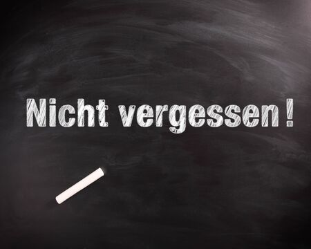 not to forget: Conceptual Nicht Vergessen or Do not Forget Phrase in White on Black Chalkboard with Chalk on Top. Stock Photo