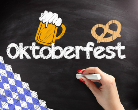 Handwritten Octoberfest Texts with Beer and Pretzel Drawing Design on Black Chalkboard photo