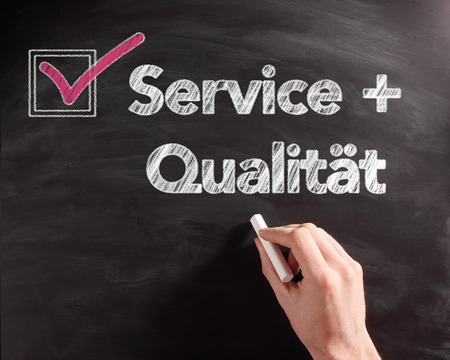 Handwritten Service and Quality Texts on Black Chalkboard with Pink Mark on Check Box. photo