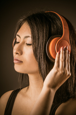 chink: Pretty Asian woman listening to music on stereo headphones with her eyes closed in bliss and her hand to her ear over a dark background