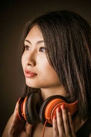 dark side: Young Asian beauty with stereo headphones around her neck staring off into space with a dreamy expression of relaxation and pleasure, closeup side view of her face over a dark background