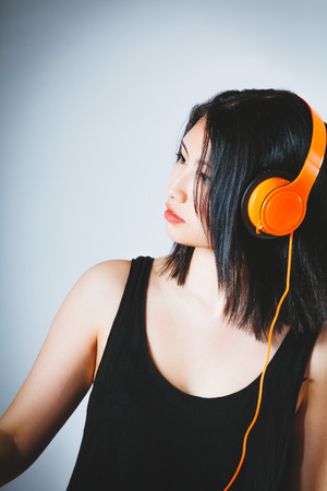 soundtrack: Attractive young Asian woman concentrating on her music as she stands listening to a soundtrack on stereo headphones, over a grey background with vignette and copyspace