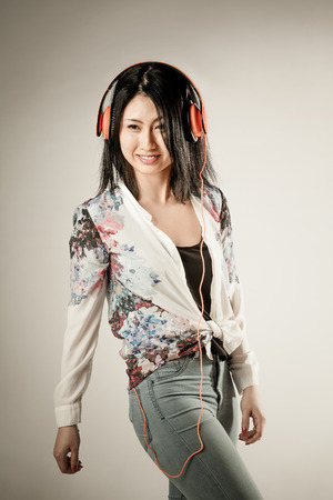 vivacious: Vivacious trendy slender young Asian woman with a charismatic playful smile enjoying her music on a set of stereo earphones over a studio background with a vignette