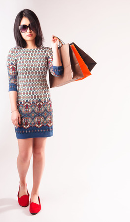 chink: Fashionable attractive young Asian woman with colorful shopping bags slung over her shoulder wearing a pretty patterned dress and sunglasses over a white background