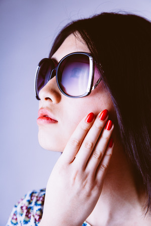chink: Fashionable gorgeous young Asian woman in trendy sunglasses with her hand to her cheek showing off her manicured nails looking to the side with a serene expression